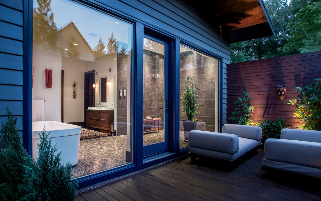 In the master suite, the open bathroom, with a tub, dual shower, and access to a private deck, is quite the dream.