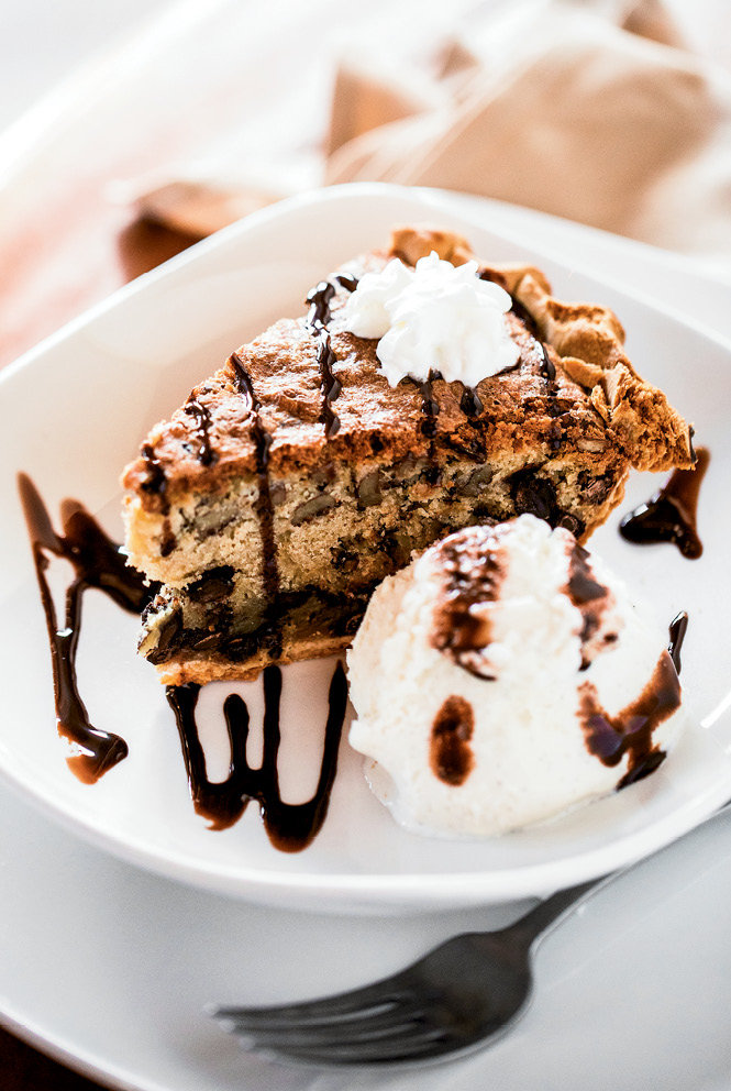 A slice of deep-dish chocolate chip pie with pecans, served warm, is accompanied by a scoop of vanilla ice cream.