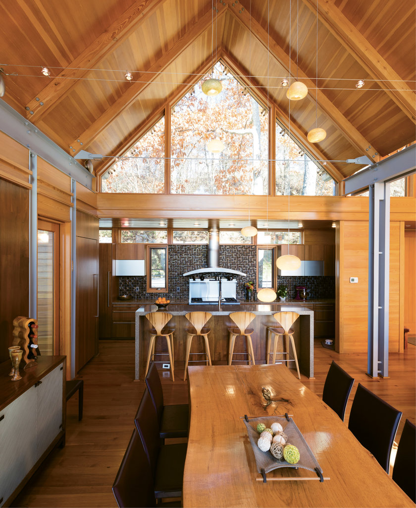 Inviting Space - Douglas fir ceilings, doors, and windows, cypress and walnut walls, and recycled center-cut heart pine floors bring warmth throughout, but particularly to the open kitchen and dining area. An iridescent glass tile backsplash adds contemporary shine.