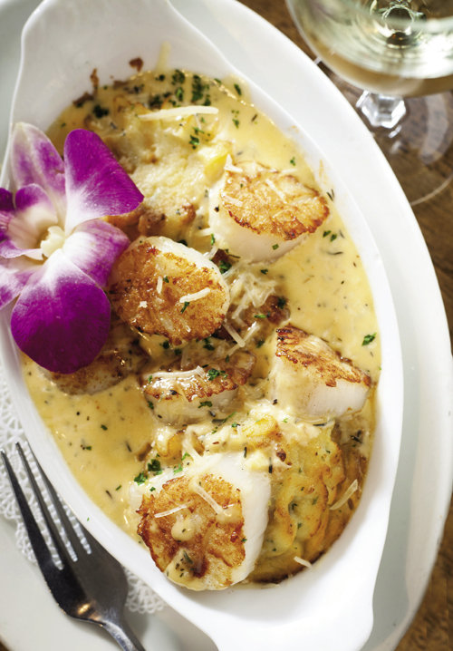 oquilles St. Jacques, a savory French dish of pan-seared scallops and lobster fumet with heavy cream and sherry, served over dutch potatoes