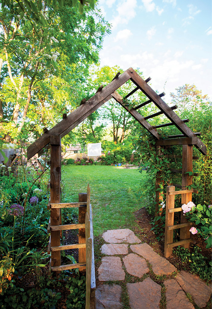 Entered via a wooden arbor, the backyard features an array of plants grown for Thomas's shop, fairy and vegetable gardens.