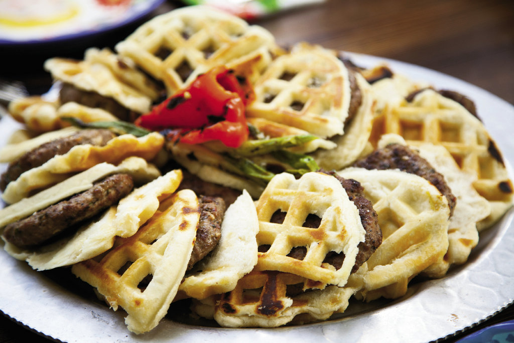Spicy lamb burgers receive the breakfast treatment with a biscuit waffle bun. Toppings include grilled halloumi cheese, grilled peppers, mustard grilled red onions, pickled beets, and a maple aioli.