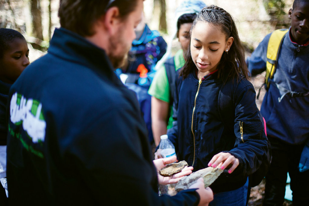 Hands On - Muddy Sneakers encourages students to interact directly with the natural world, bringing new life to lessons taught in the classroom. Here, instructor Davis Hayden examines differences in the types of rocks found at Eagle Point Nature Preserve with students from Isenberg Elementary in Salisbury.