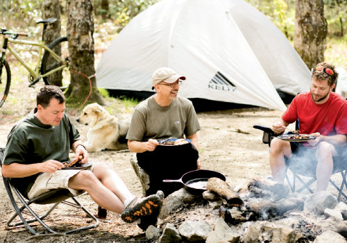 Ben Butler, Tom Gallo, and Jeff Dingus swap cycling tales over breakfast calzones and blue flannel hash at the campsite deep in Pisgah National Forest, which is known for its challenging bike trails.