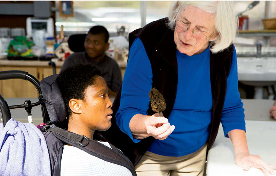 Connecting to Nature - Retired special  education teacher Mary Hugenschmidt shows a seedpod to Terriona Dula. The program exposes participants to the natural world.