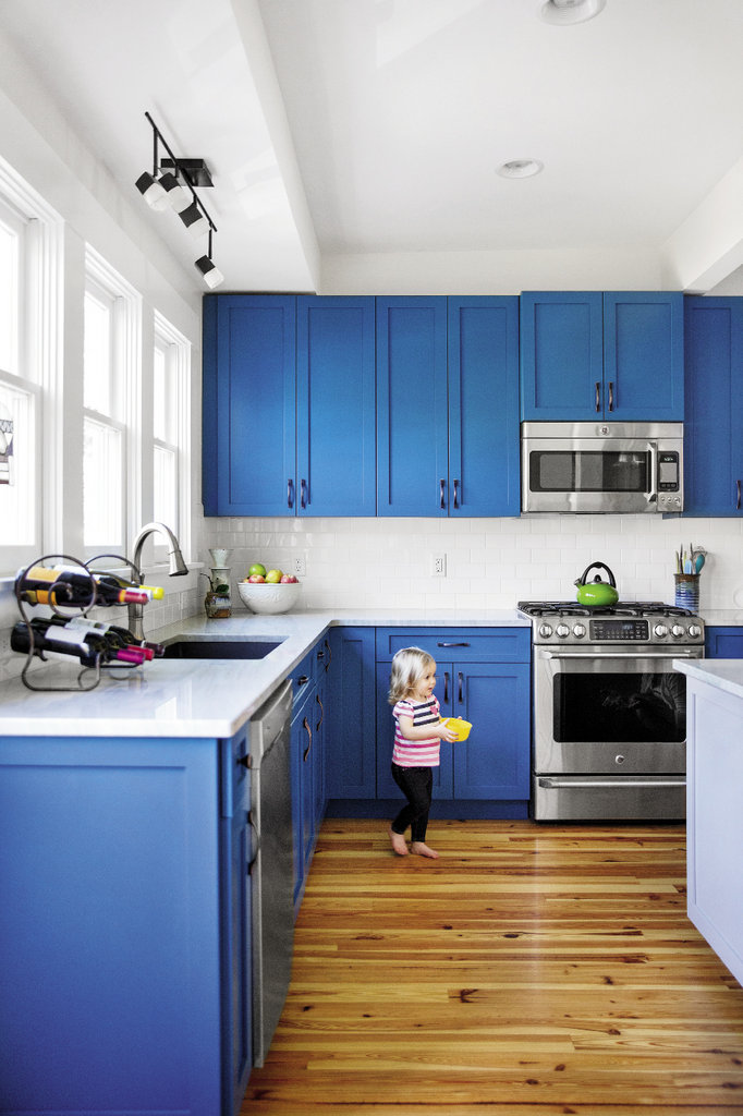 The Palmes opened up the kitchen by removing walls between it and the dining room and adding windows. Clean white tiles against sharp blue cabinets further brighten the space.