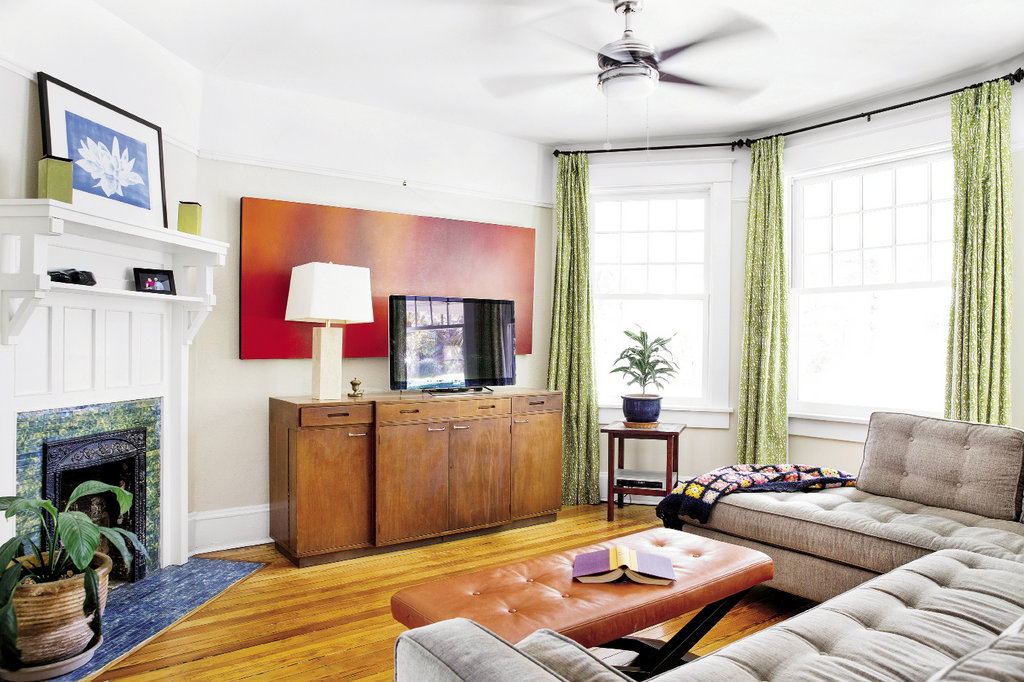 In the living room, mid-century modern-style furnishings and two works of art by Kevin speak to the couple's clear aesthetic.