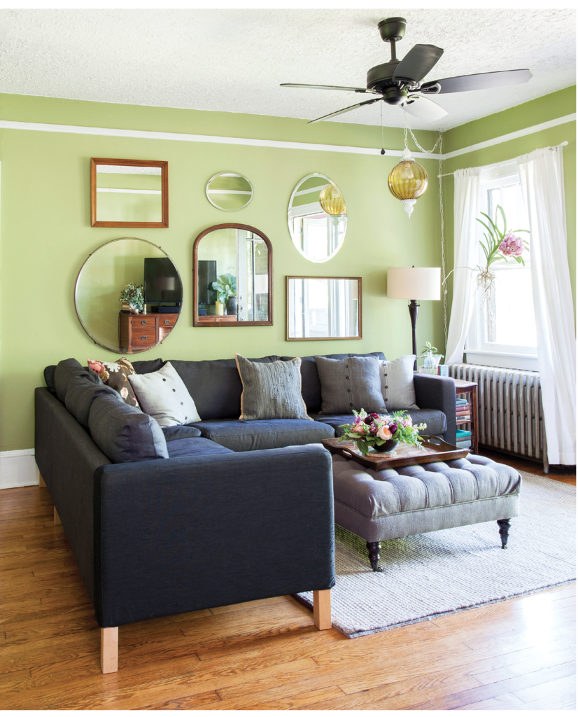 In the living room, where a brilliant vanda orchid hangs in the window, antique and vintage mirrors help bring light and a sense of spaciousness to the small room. A sectional Ikea sofa is great for family movie nights.