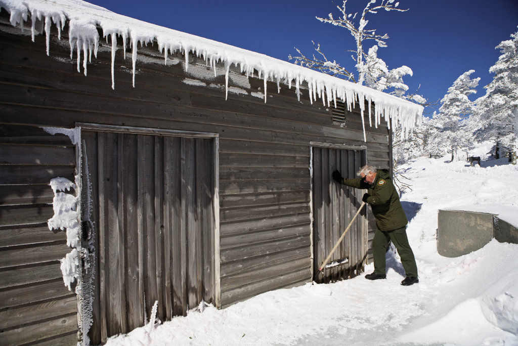 Larry Blevins scrapes away snow to dislodge a frozen door on a gear shed.