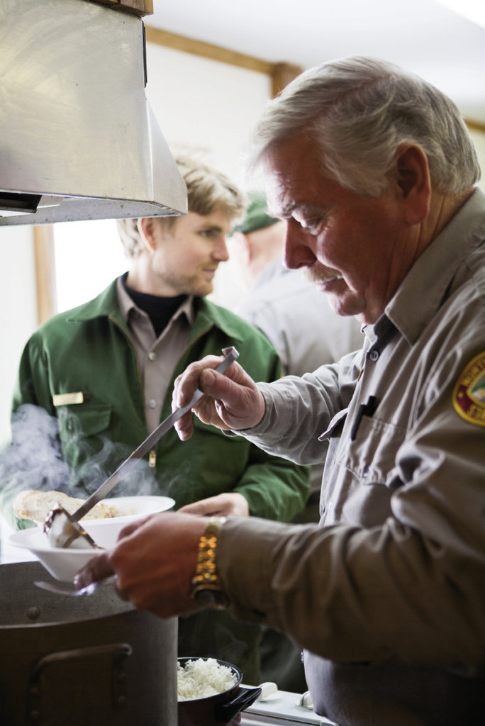 Larry Blevins ladles steaming soup during the Mardi Gras meal for rangers and park staff.
