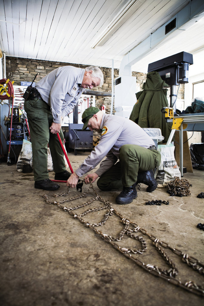 Larry Blevins and Wade Barnett repair tire chains that keep park vehicles from sliding on the road.