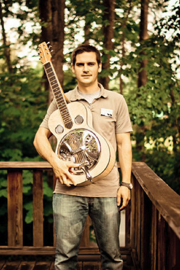Folk School staff member Reed Caldwell with the resonator guitar he made in a class at the Brasstown campus.