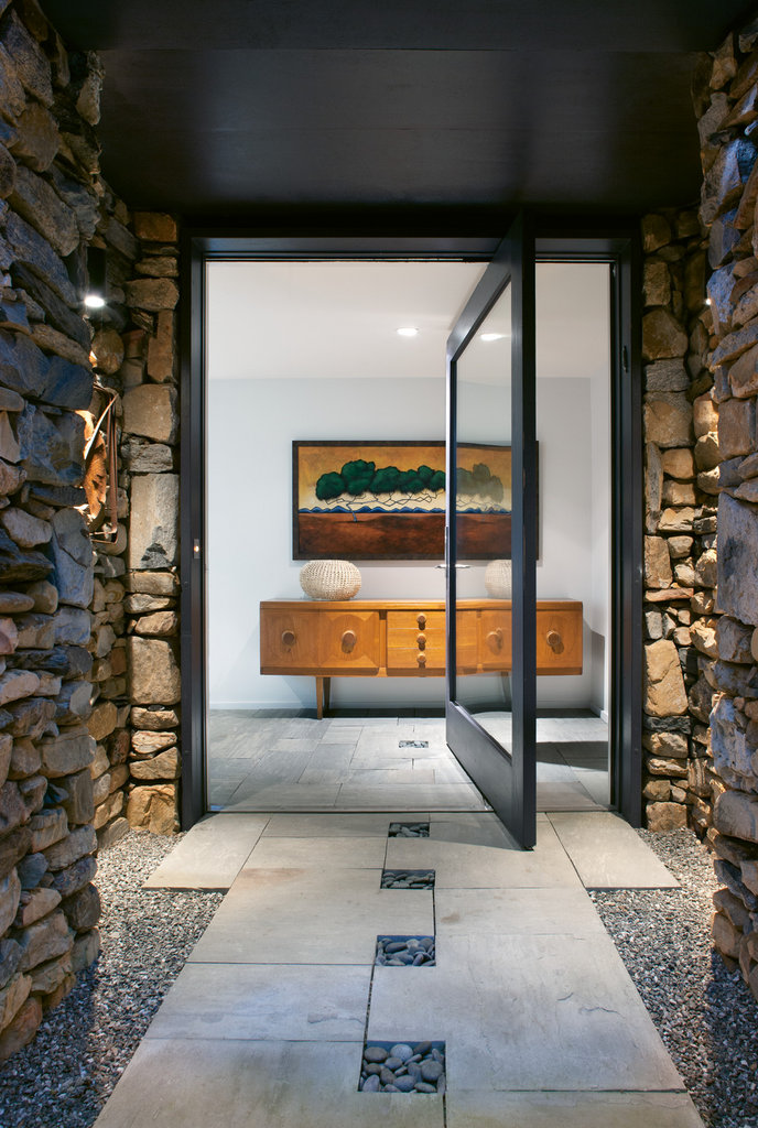 To create the modern and inviting lower-level entry, a set of stairs and office door were relocated. Now a clean wall punctuated by a handsome console and painting by Philip DeAngelo welcome visitors. An offset pivot door and the continuation of tile, including the inset of Mexican beach pebbles, into the foyer blends the exterior and interior spaces.