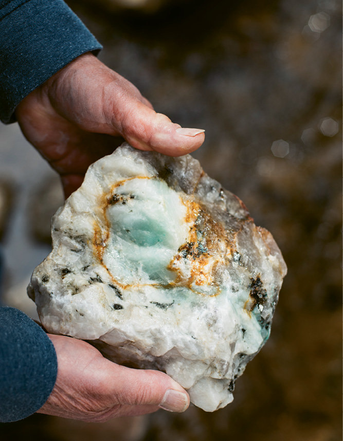 This pegmatite, estimated to be 380 million years old, contains feldspar (the white), blue-green malachite, shiny black mica, and brown streaks indicating uranium ore.