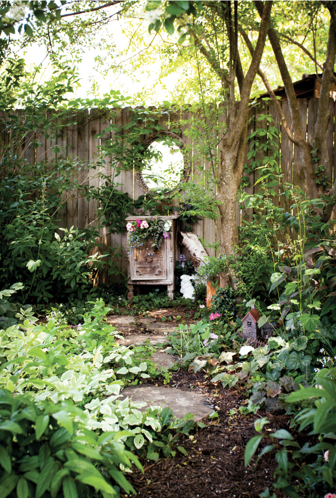 The fenced backyard garden is a dream. Among the features is Annabelle's fairy garden (top), where an old side table and mirror add intrigue.