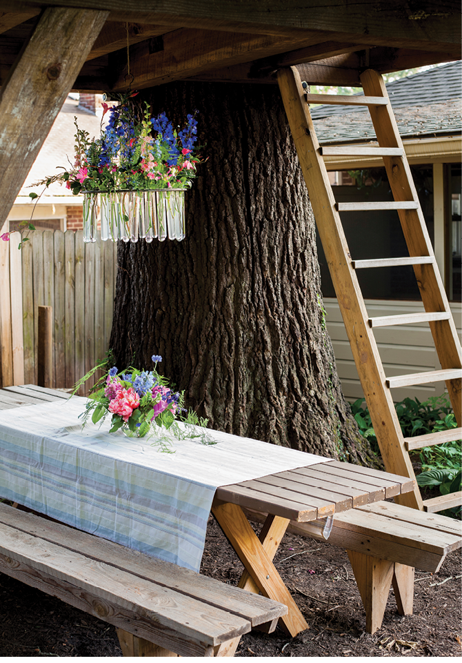Underneath, a rustic picnic table is made elegant with blooms and a