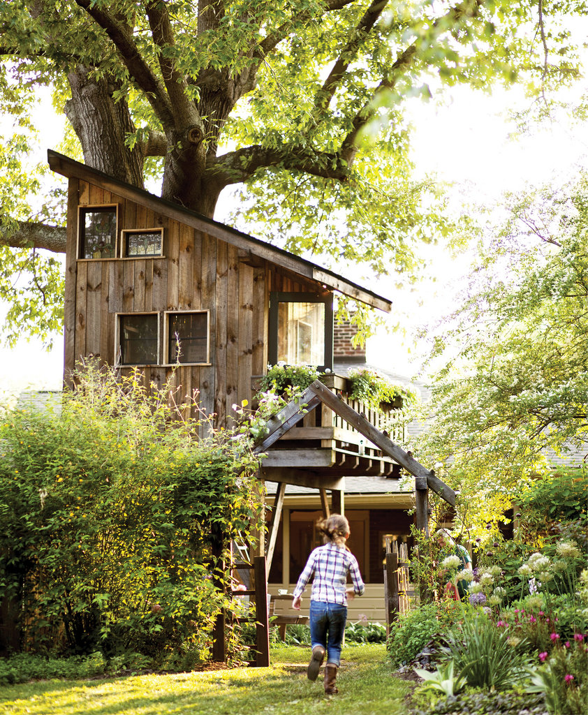 An adorable eight-by-eight-foot, two-story tree house, complete with a sitting room and sleeping loft, towers over the Thomases' lush backyard garden in West Asheville.