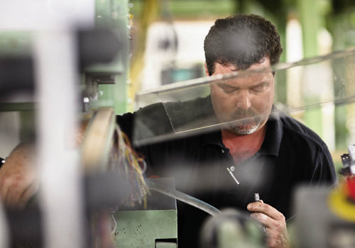 Overhauler Barry  Connor (below) knows the machines inside and out, diagnosing and fixing problems to keep the looms running.
